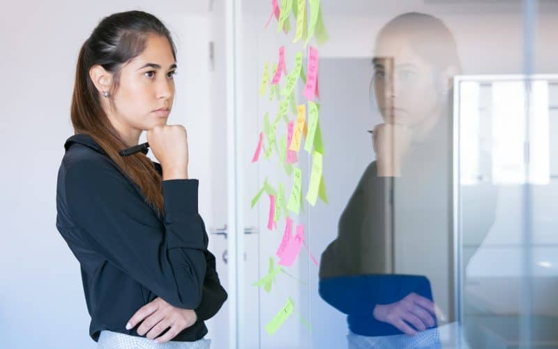 thoughtful latin businesswoman holding marker and reading notes on glass wall focused confident pretty female worker in suit thinking about idea for project