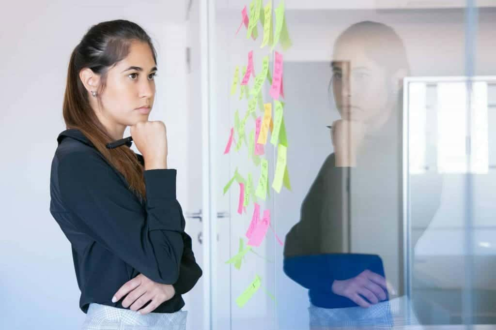 thoughtful latin businesswoman holding marker and reading notes on glass wall focused confident pretty female worker in suit thinking about idea for project scaled