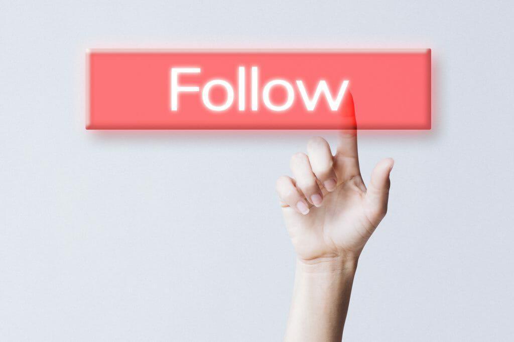 hand clicking follow button social media